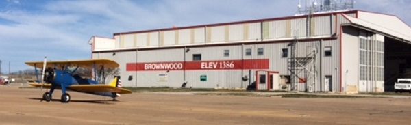 A small biplane sits parked in front of a hanger that reads Brownwood Elev 1386
