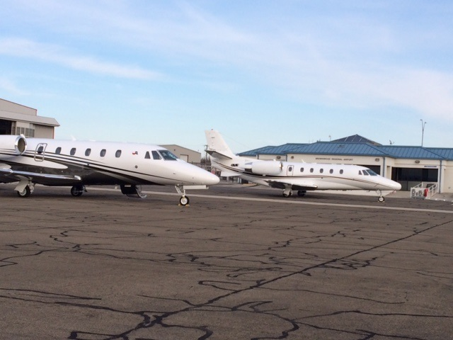 2 small passenger planes parked at the regional airport.